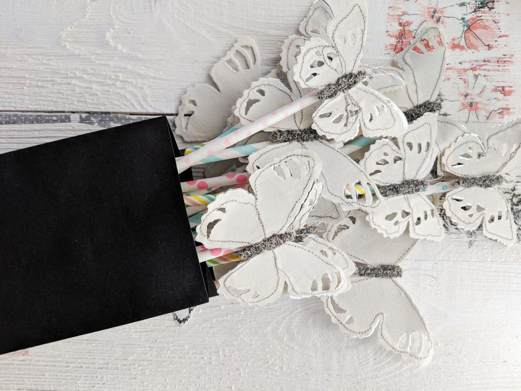 bag of butterflies clipped to colorful paper straws