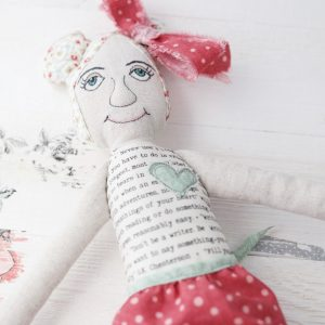cloth doll with text fabric and embroidered face